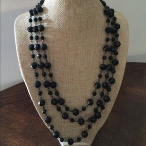 Black multi strand beaded necklace.